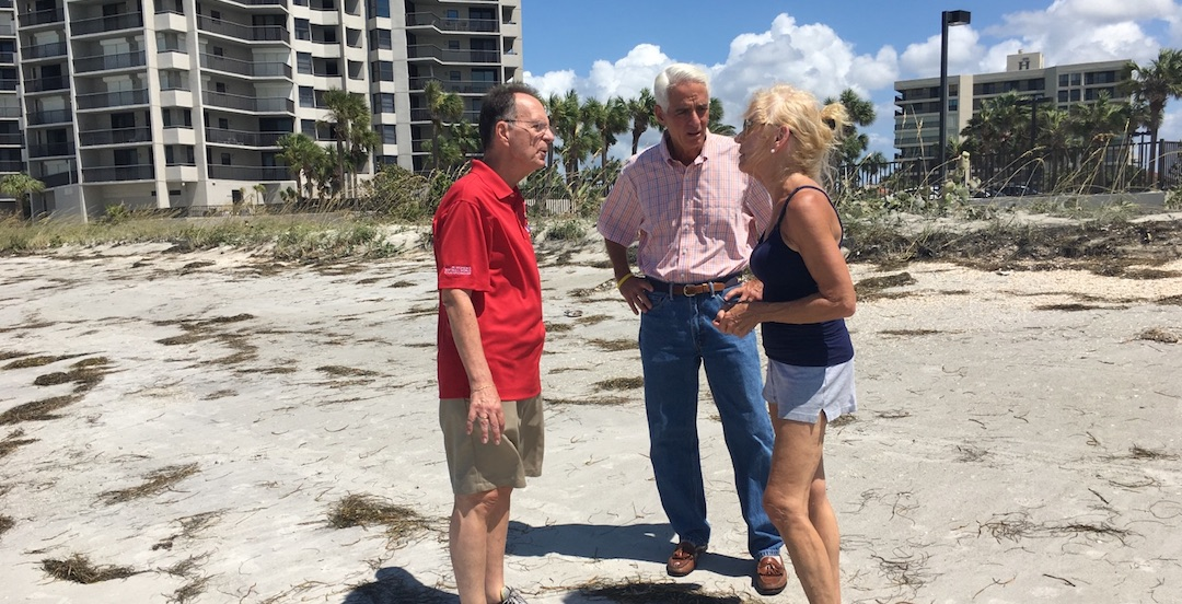 Rep. Charlie Crist speaking with constituents on the beach.